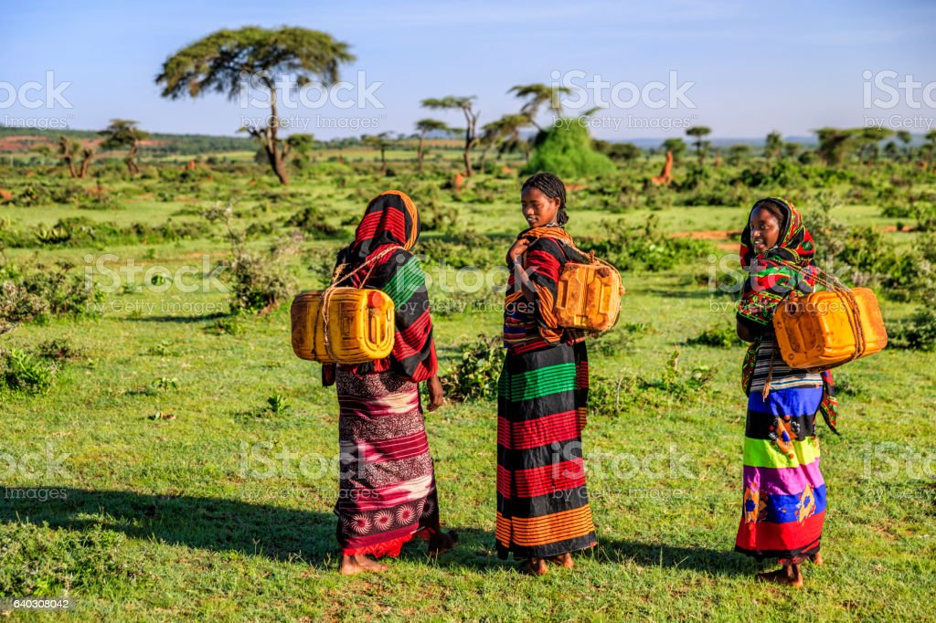 Young African women carrying water from the well, Ethiopia, Africa stock photo