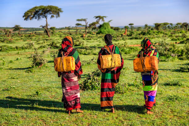 young african women carrying water from the well, ethiopia, africa - horn of africa stock photos and pictures