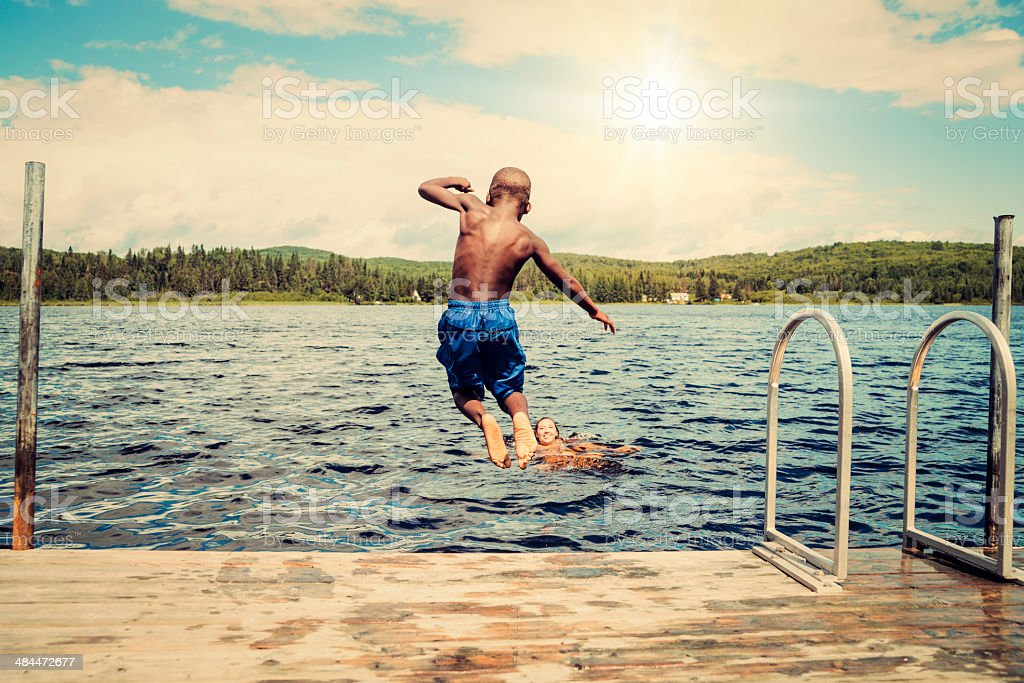 Young african-american boy jumping from a pier in lake. stock photo