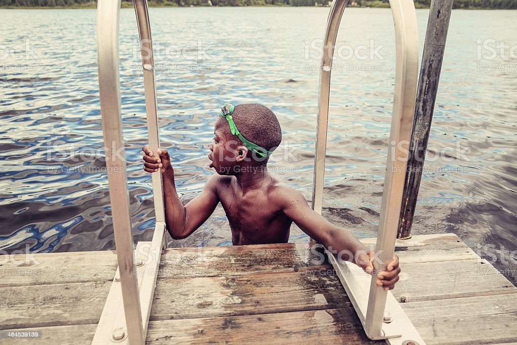 Young african-american boy with goggles swimming in lake. stock photo