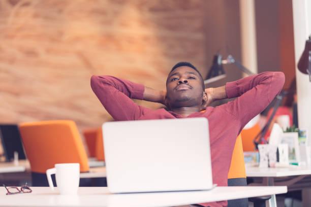 giovane afroamericano uomo d'affari prendendo una pausa alla sua scrivania - divano procrastinazione foto e immagini stock
