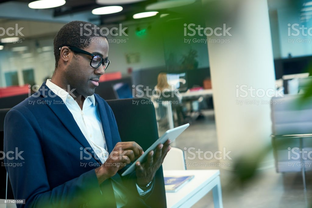 Young African-American Businessman Using Tablet in Office stock photo