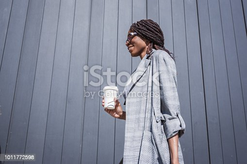 istock Young, African-american businesswoman walking from the airport 1011772598