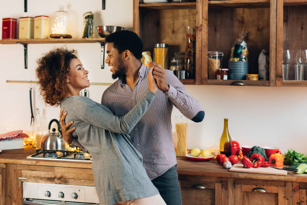 Young african-american couple dancing in kitchen, copy space stock photo