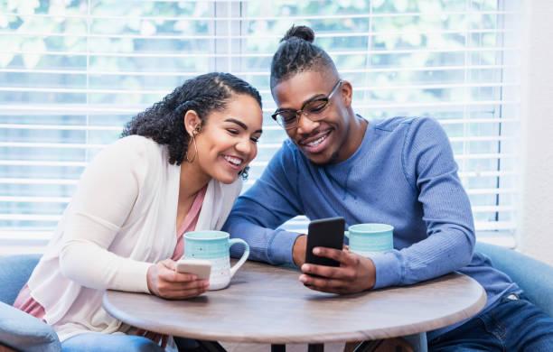 joven pareja afroamericana, compartiendo teléfono móvil - happy couple sharing a cup of coffee fotografías e imágenes de stock