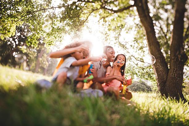 junge afroamerikanische familie lachen blasen blasen und toget - kinder picknick spiele stock-fotos und bilder
