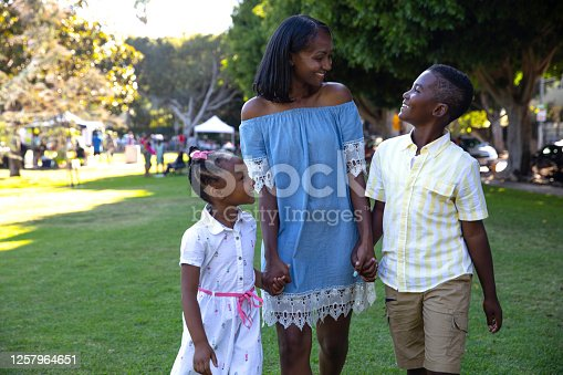 istock Young african-american family walking in a park 1257964651