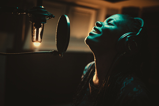 One beautiful young African-american female singer recording album in the professional music studio. Female vocalist wearing headphones and singing into microphone in recording studio.