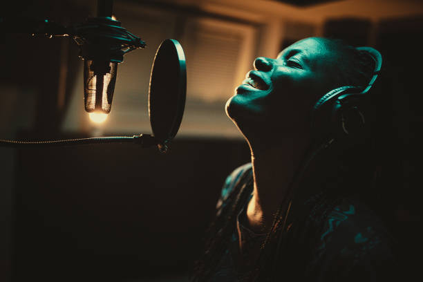 Young African-american female singer recording song in the music studio stock photo