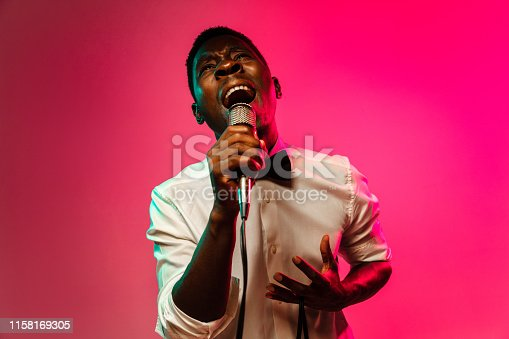 Young african-american jazz musician singing a song on gradient pink-red background in neon light. Concept of music, hobby, festival, open-air. Joyful guy improvising. Colorful retro portrait of singer.