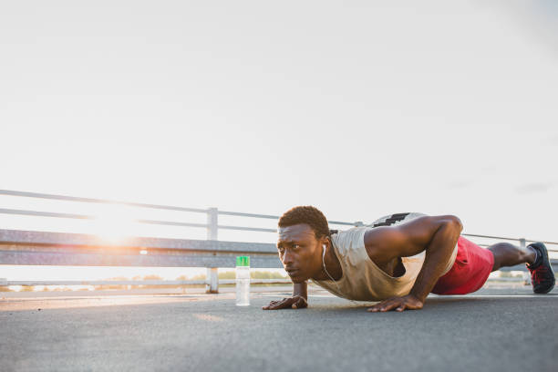 Young African-American male doing push-ups, outdoors stock photo