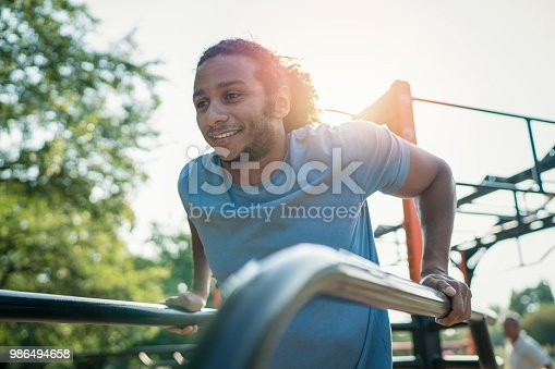 istock Young African-American male training arm muscles in the park 986494658