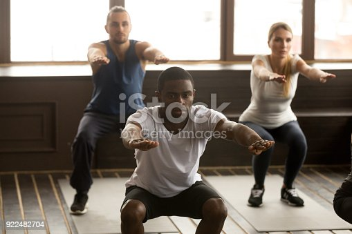 istock Young african-american man doing squat exercises at group fitness training 922482704
