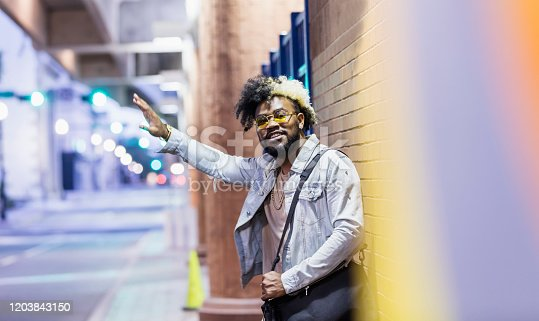 istock Young African-American man in the city hailing ride 1203843150