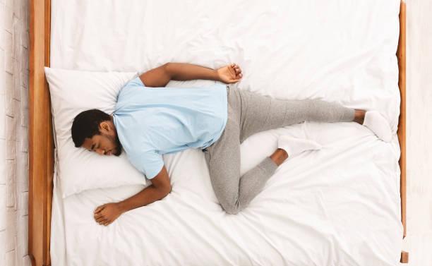hombre joven afroamericano durmiendo en la cama vista superior - man sleeping fotografías e imágenes de stock