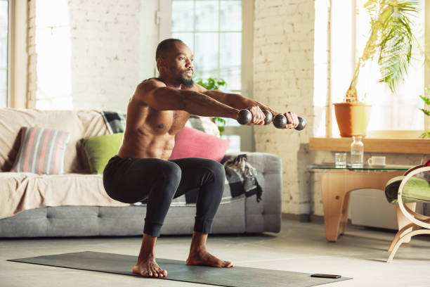 Young african-american man teaching at home online courses of fitness, aerobic, sporty lifestyle while being quarantine stock photo