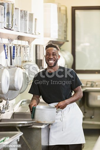 istock Young African-American man working in commercial kitchen 1049509168