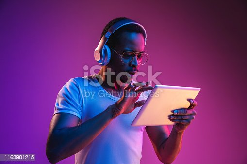 istock Young african-american man's listening to music in neon light 1163901215
