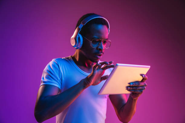 Young african-american man's listening to music in neon light stock photo