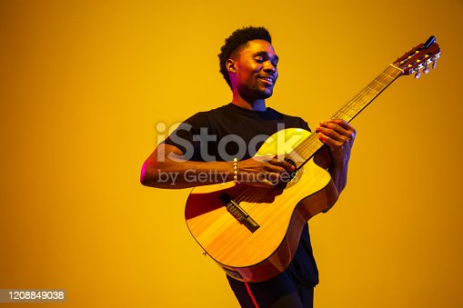 Young and joyful african-american musician playing guitar and singing on gradient orange-yellow studio background in neon light. Concept of music, hobby, festival. Colorful portrait of modern artist.