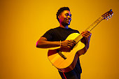 istock Young african-american musician singing, playing guitar in neon light 1208849038