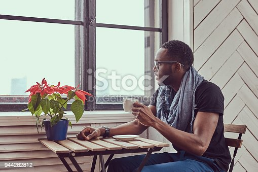istock Young African-American student drinks morning coffee sitting at 944282812