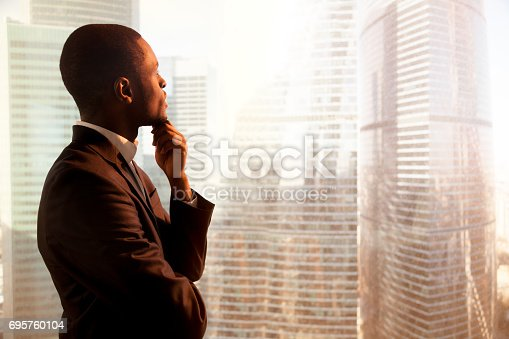 istock Young african-american thoughtful businessman looking through window on sunset city 695760104