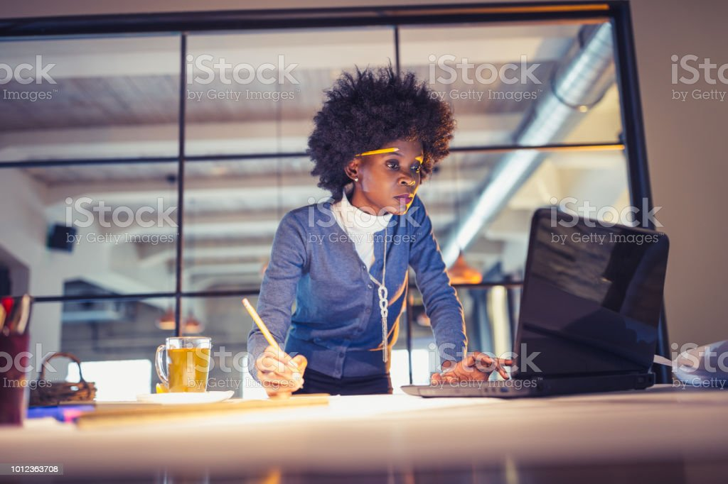 Young African-American woman architect working late in office stock photo