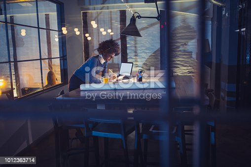 918035432 istock photo Young African-American woman architect working late in office 1012363714