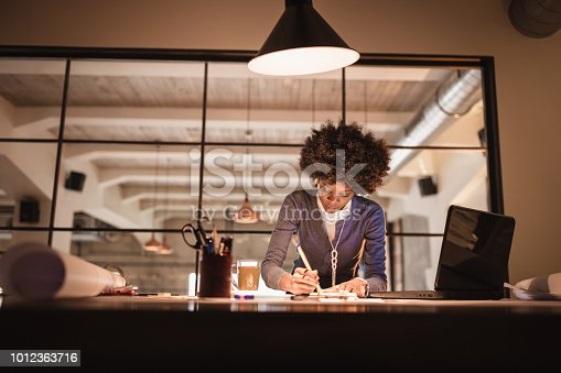 918035432 istock photo Young African-American woman architect working late in office 1012363716
