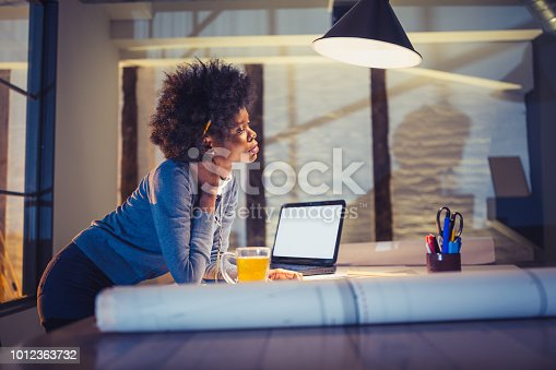 918035432 istock photo Young African-American woman architect working late in office 1012363732