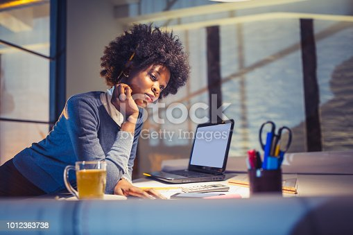 918035432 istock photo Young African-American woman architect working late in office 1012363738