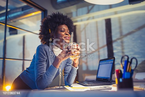 918035432 istock photo Young African-American woman architect working late in office 1012363744