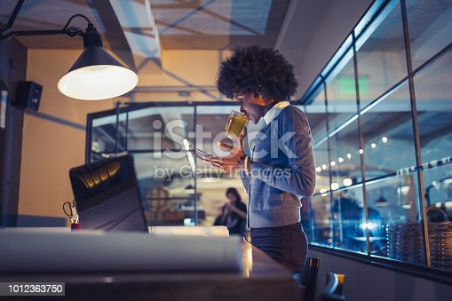 918035432 istock photo Young African-American woman architect working late in office 1012363750