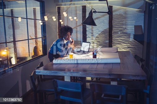 918035432 istock photo Young African-American woman architect working late in office 1012363752