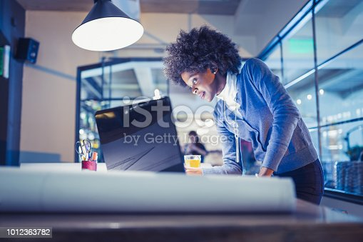 918035432 istock photo Young African-American woman architect working late in office 1012363782