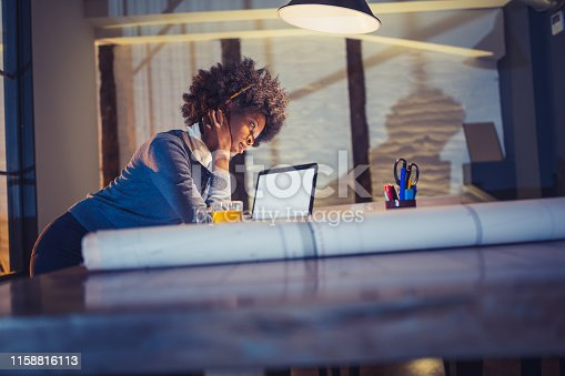 918035432 istock photo Young African-American woman architect working late in the office 1158816113