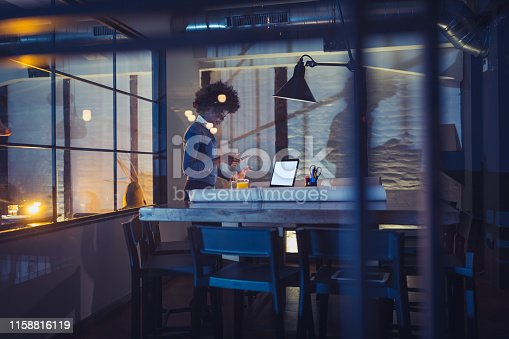 1012363738 istock photo Young African-American woman architect working late in the office 1158816119