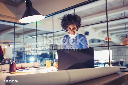 918035432 istock photo Young African-American woman architect working on a project. 1036803286