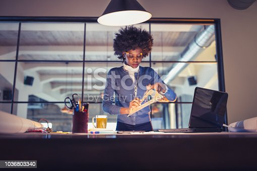 918035432 istock photo Young African-American woman architect working on a project. 1036803340