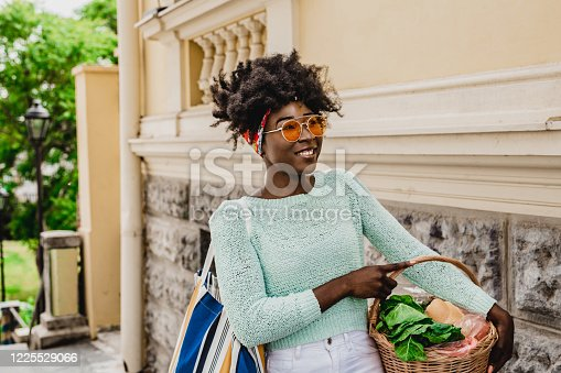 A modern smiling african-american woman is holding a basket full of groceries