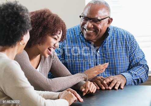 istock Young African-American woman conversing with her parents 914626022