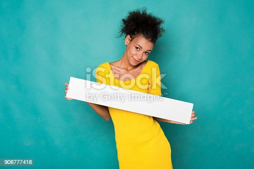 istock Young african-american woman holding blank banner 906777416