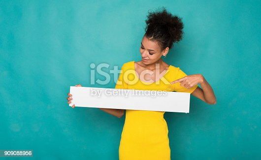 istock Young african-american woman holding blank banner 909088956