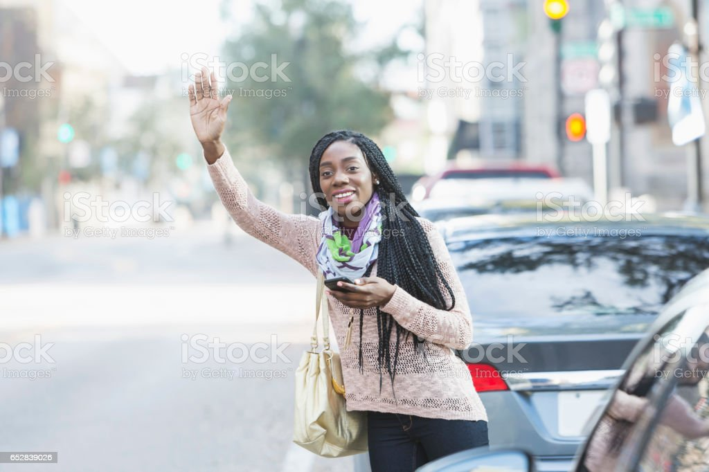 Young African-American woman in city looking for her ride stock photo