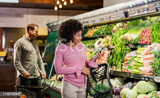 istock Young African-American woman shopping in grocery store 1145100487