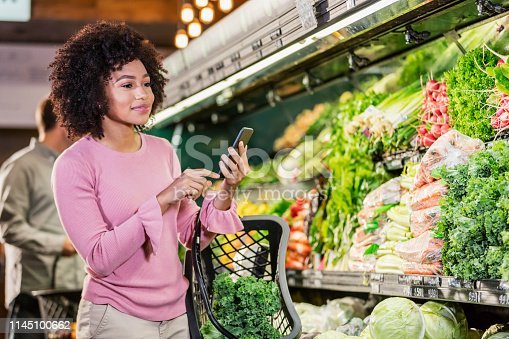 istock Young African-American woman shopping in grocery store 1145100662
