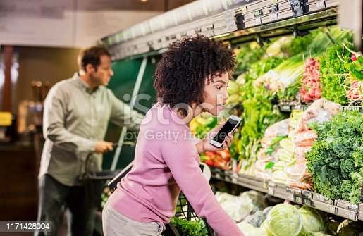 istock Young African-American woman shopping in grocery store 1171428004