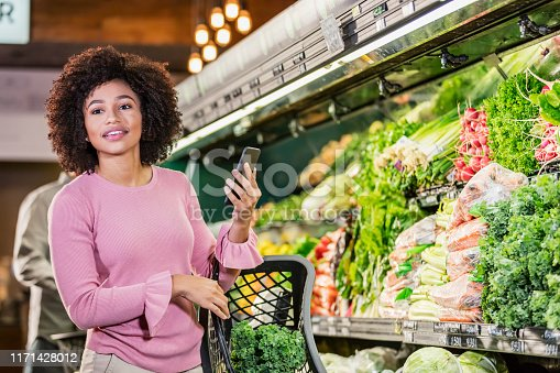 istock Young African-American woman shopping in grocery store 1171428012