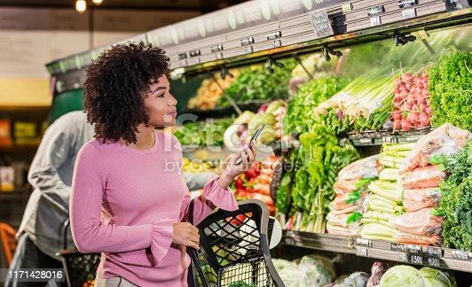 istock Young African-American woman shopping in grocery store 1171428016